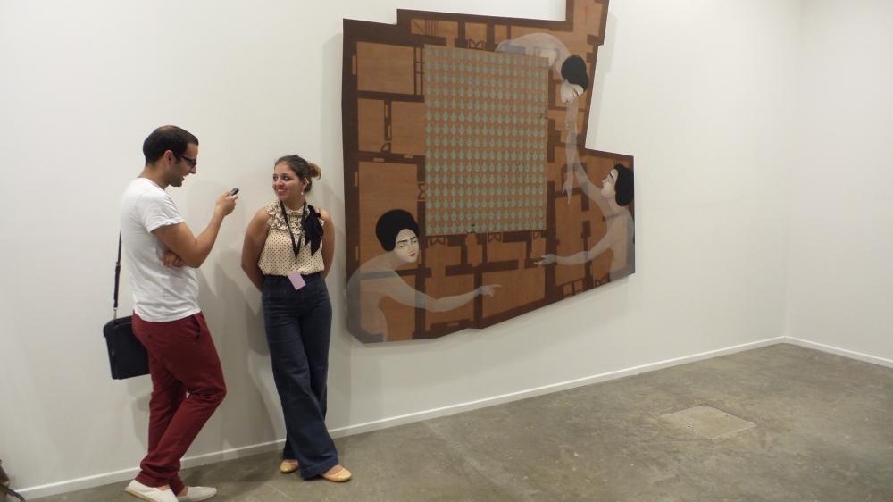 Artist Ibi Ibrahim & Al Mahha Art Founder, Mashaael Basheer posing next to Hayv Kahraman artwork