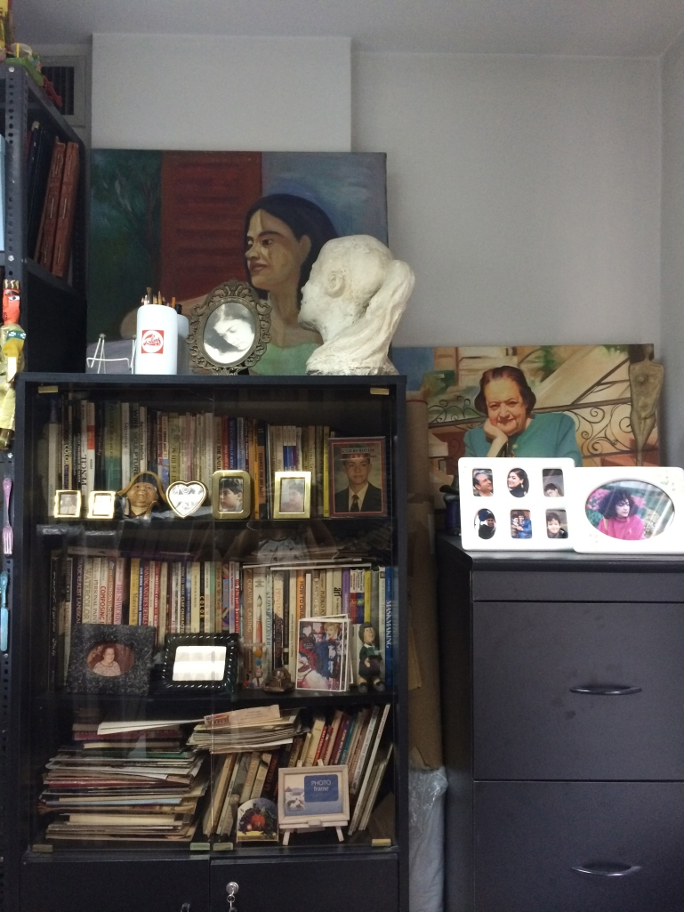 A photograph of Ginane's mother in the back and portrait of artist with valuable collection of art books